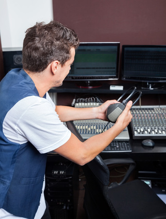 masters of rock: Side view of young man holding headphones while sitting at mixing table in recording studio Stock Photo