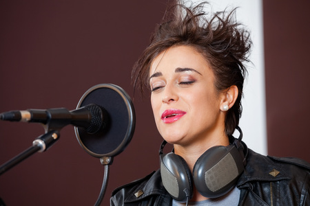 spiked hair: Smiling young woman with eyes closed singing in recording studio