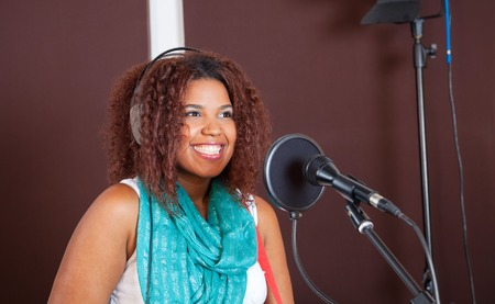professional practice: Young female singer smiling while performing in recording studio Stock Photo
