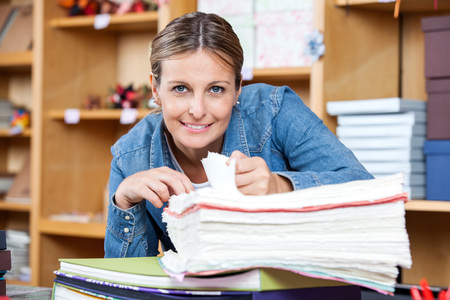 paper craft: Portrait of smiling female customer analyzing papers in store