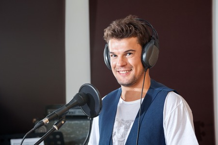 vocalist: Portrait of smiling young male singer in recording studio Stock Photo