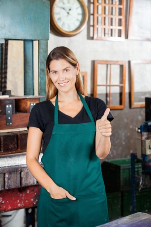 happy workers: Portrait of female worker showing thumbs up while standing in paper factory Stock Photo