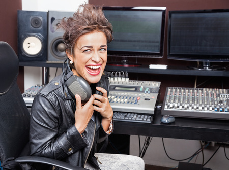 spiked hair: Young female professional laughing while sitting at mixing desk in recording studio Stock Photo