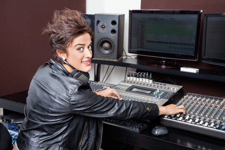 spiked hair: Portrait of confident young woman mixing audio in recording studio