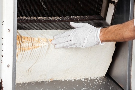 food industry: Cropped image of male bakers hand touching bread in slicing machine at bakery