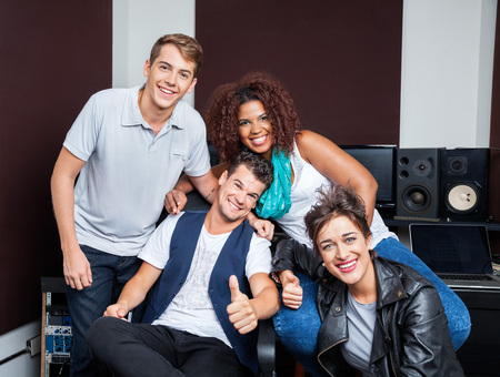 masters of rock: Portrait of happy multiethnic musicians in recording studio