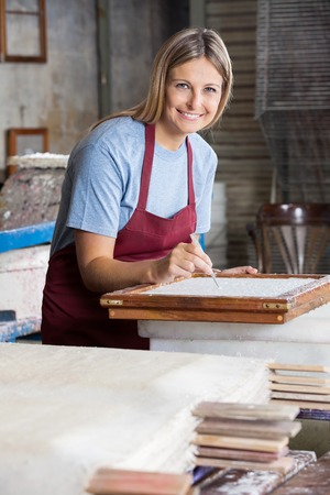 deckle: Portrait of smiling female worker cleaning paper with tweezers in factory Stock Photo