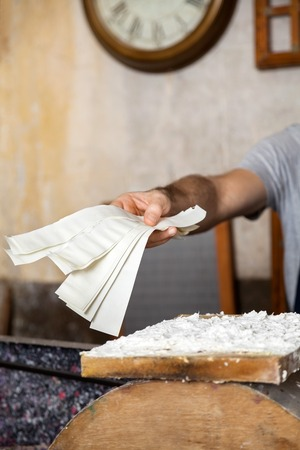 Cropped image of worker giving paper strips in factory
