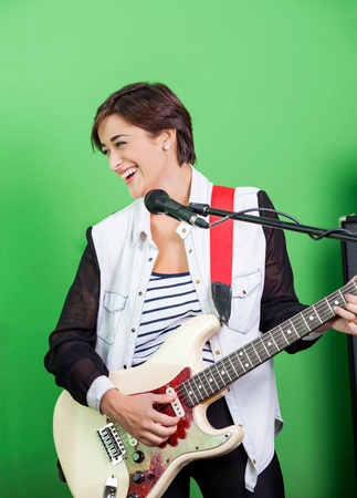 signer: Happy female signer playing guitar while singing in recording studio