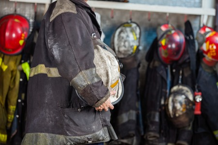 midsection: Midsection side view of fireman holding helmet at fire station