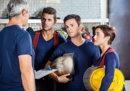 fireman: Mature fireman discussing plan with team at fire station Stock Photo