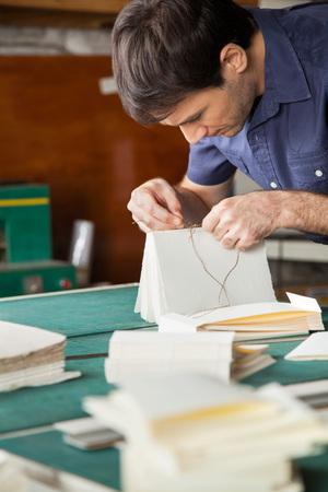 Mid volwassen mannelijke arbeider band boek aan tafel in een papierfabriek Stockfoto