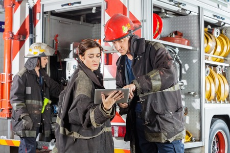 Male and female firefighters using tablet computer against truck at fire station Standard-Bild