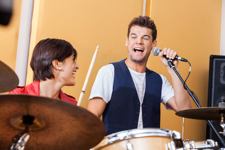 drumset: Happy male singer performing while looking at female drummer in studio