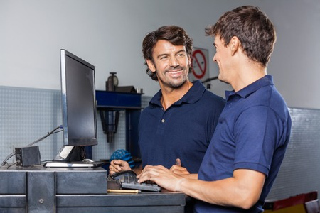 data entry: Happy male mechanic discussing with colleague while using computer in garage Stock Photo