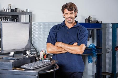 tecnología informatica: Retrato de la sonrisa de pie brazos mecánicos masculinos cruzados por computadora en taller de reparaciones auto