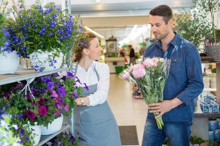 salesgirl: Salesgirl assisting male customer in buying flower bouquet at store