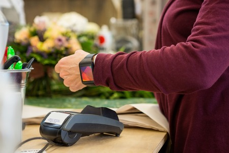 retail: Cropped image of female customer paying through smart watch at flower shop