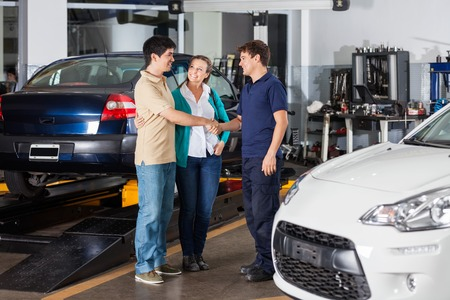 auto repair: Happy mechanic shaking hand with couple at auto repair shop Stock Photo
