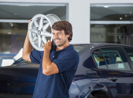 Smiling male technician while carrying metallic alloy on shoulder at auto repair shop