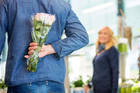 dar un regalo: Vista trasera del hombre esconde ramo de la mujer en la tienda de flores