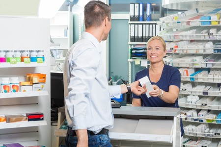 farmacia: Sonreír químico dando femenina producto al cliente masculino en la farmacia