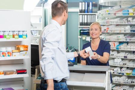 Sorridente femminile chimico dando prodotto al cliente maschio in farmacia