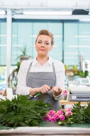 arranging: Portrait of confident female florist cutting stem on rose in flower shop