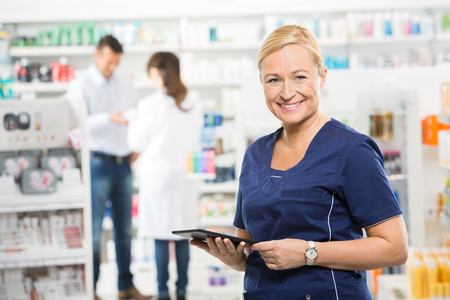 Portrait of happy assistant holding digital tablet while pharmacist and customer standing in background at pharmacy