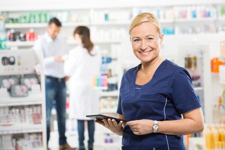 farmacia: Retrato de feliz asistente sostiene la tablilla digital mientras farmacéutico y el cliente pie en segundo plano en la farmacia