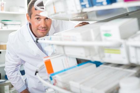 farmacia: Retrato del qu�mico de sexo masculino confidente contando acciones en farmacia