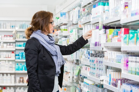 farmacia: Comprador femenina del adulto mediados de elegir un producto en la farmacia