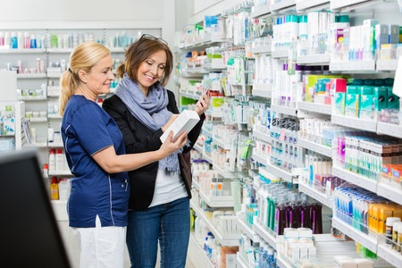 pharmacy store: Smiling female assistant showing product to customer holding cell phone in pharmacy Stock Photo