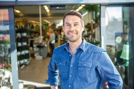 Portrait of confident man standing outside flower shop Stock fotó