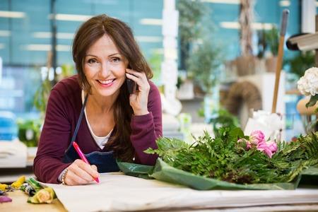 꽃이 게에서 종이에 작성하는 동안 휴대 전화를 사용 하여 행복 한 여성 플로리스트의 초상화