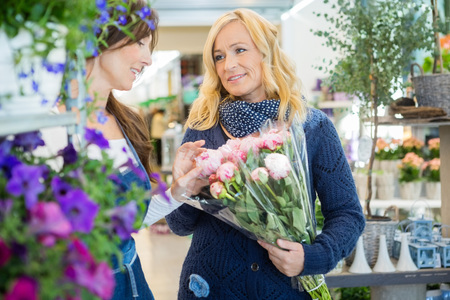 buying: Florist assisting female customer in buying flower bouquet at store