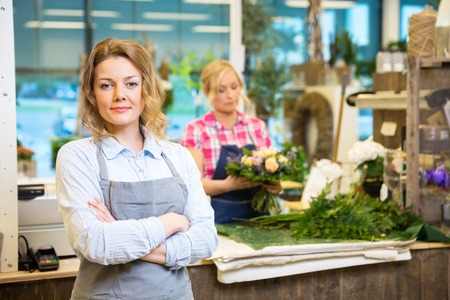 working hands: Portrait of confident female owner with worker in background at flower shop