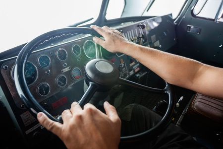 Cropped image of firemans hands holding steering wheel of firetruck at station