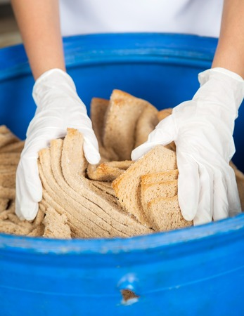 food industry: Closeup of womans hands discarding bread waste in garbage bin at bakery