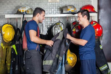 bombero: Bomberos felices mirando el uno al otro, mientras que la celebraci�n de la chaqueta en la estaci�n de bomberos