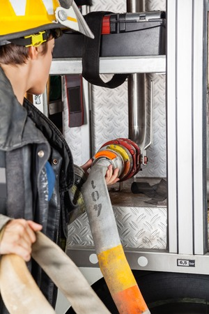 firetruck: Young female firefighter fixing water hose in firetruck at station Stock Photo
