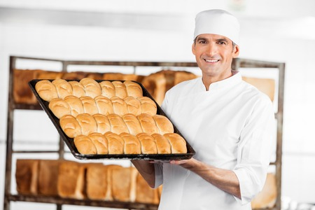 Portrait of smiling mature baker showing breads in baking tray at bakery