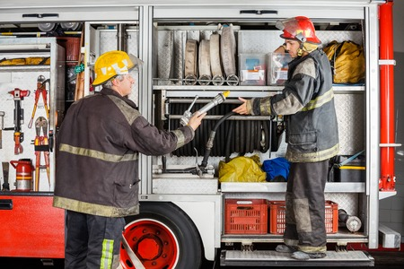 engine fire: Mature and young firefighters working at truck in fire station