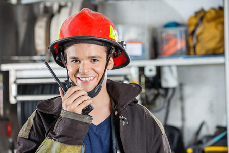 Portrait of happy young fireman using walkie talkie at fire station