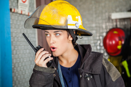 talkie: Confident young firewoman looking away while using walkie talkie at fire station