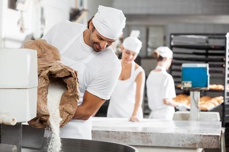 cocinas industriales: Varón sonriente panadero harina de verter en la máquina de amasar en la panadería Foto de archivo
