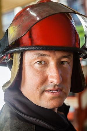 casco rojo: Primer retrato de bombero confianza llevaba casco de color rojo en el parque de bomberos Foto de archivo