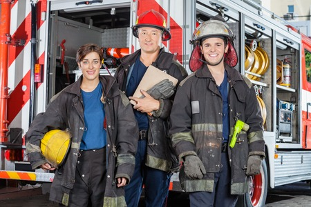 standing against: Portrait of confident firefighters standing against truck at fire station Stock Photo