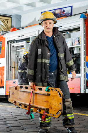 firefighter: Full length of confident male firefighter carrying wooden stretcher against truck at fire station