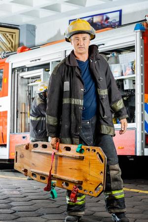 bombero: Longitud total de bombero masculina conf�a en llevar la camilla de madera contra el cami�n en la estaci�n de bomberos